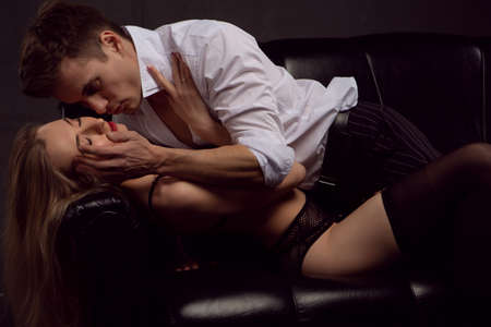 Young attractive couple kissing in a passionate embrace lying on a black leather sofa