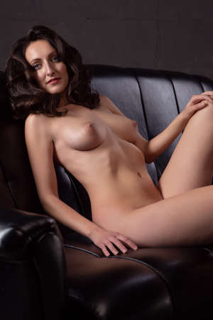 Gorgeous young brunette woman lies on a black leather sofa