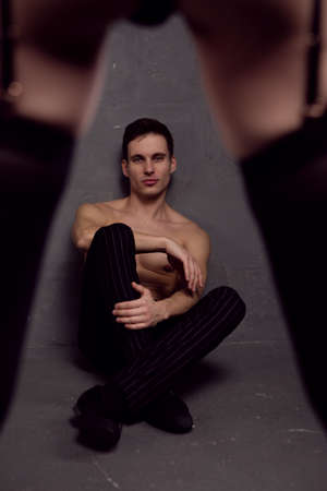 a young handsome man with a athletic torso sits on the floor in front of a woman in underwear and stockings