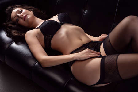 Portrait of a young brunette woman posing in lace underwear on a black leather sofa