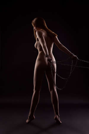 gorgeous chained and young woman with a beautiful body on a dark background