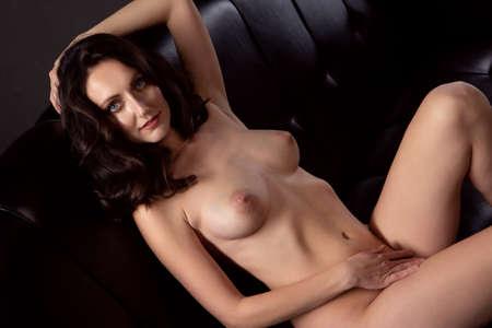 Sexy brunette woman lying on a black sofa