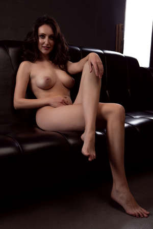 Gorgeous young brunette woman lies on a black sofa