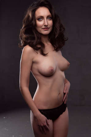 Gorgeous young brunette woman with body on dark background