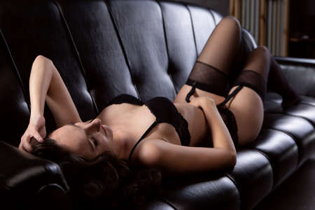 Gorgeous young woman in black underwear lies on the sofa