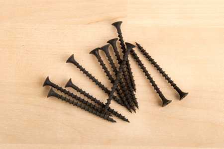 Black wood screws on wooden background. Building material.