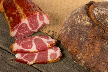 A loaf of grey bread and meat on a wooden background Zdjęcie Seryjne
