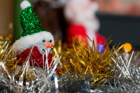 the tinsel: Snowman among festive tinsel Stock Photo