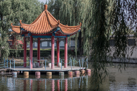 arbor: The Chinese arbor on water in a willow environment Stock Photo
