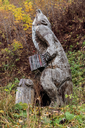 Wooden figure of a bear with an accordion in city park