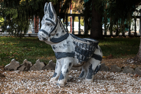 burro: Sculptures of a little burro with baskets in park Stock Photo