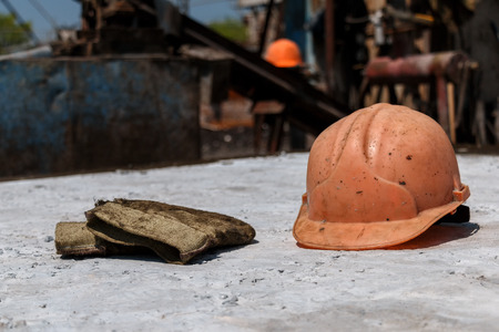 A yellow protective helmet and mittens lie during a lunch break Stock Photo