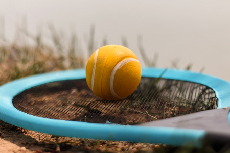 nylon string: The yellow tennis ball and racket lie on a grass