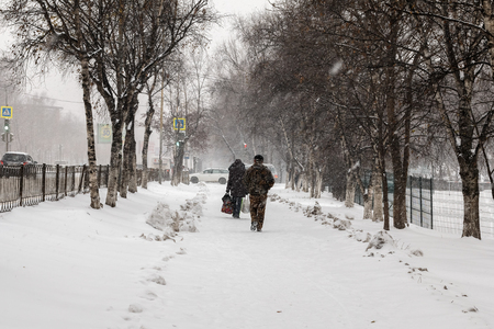 passerby: Snowfall in November on city streets Stock Photo