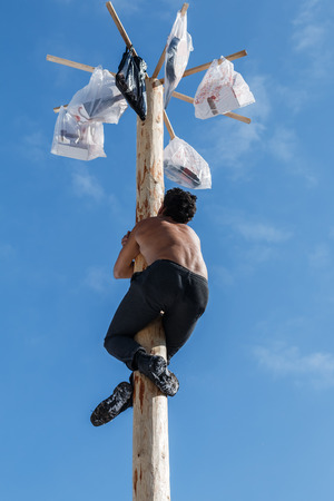 The young man climbs up a column behind festive gifts