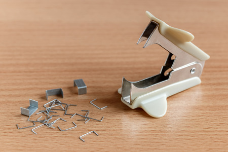 office stapler: anti-stapler and paper clips on a wooden table