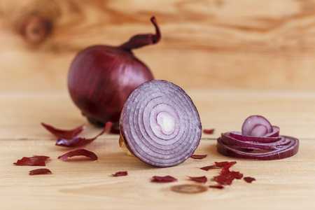 Bulbs of red onions on a wooden table Stockfoto