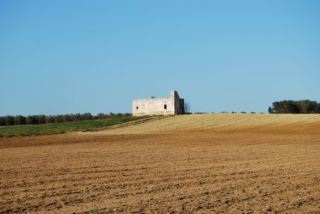 A country house surrounded by a ploughed field photo