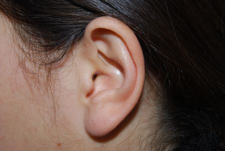 muff: A girls ear with hairs around Stock Photo