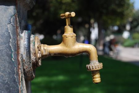 Water tap of a fountain in a park photo