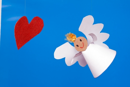 Paper toy boy angel and heart on a blue background Banque d'images