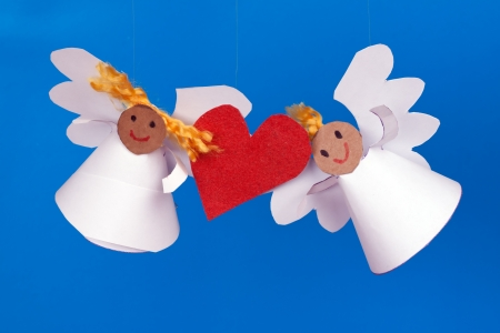two toy angel and a heart on a blue background