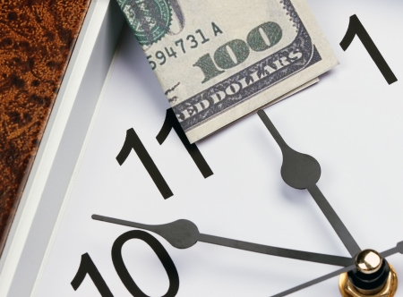 time is money hour hand points to the U S  hundred dollar bill