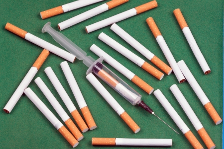 nicotine dependence metaphorsyringe loaded cigarette and a few cigarettes lying on a green surface