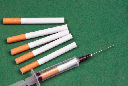 dependence: nicotine dependence metaphorsyringe loaded cigarette and a few cigarettes lying on a green surface