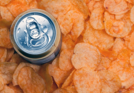 closed can of beer and chips.Focus on the can of beer