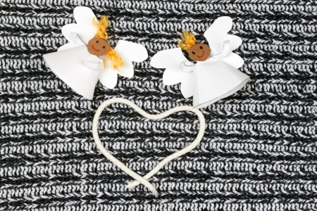 Two cheerful paper angel and heart on monochromebackground