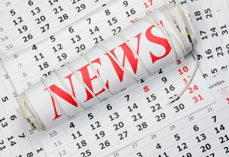 news Roll of newspapers tied with a rope lying on the calendar