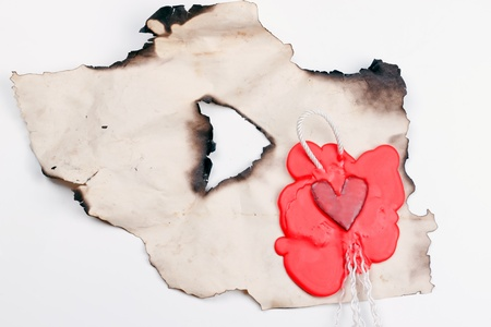 mark in the shape of a heart made of red wax on a piece of burnt paper Banque d'images