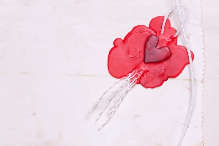 mark in the shape of a heart made of red wax on the background of old paper