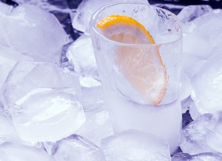 Vodka with lemon poured in a glass made of ice