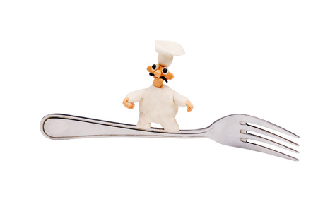 little cheerful chef made of plasticine sitting on a fork