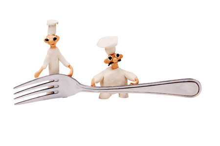 three little cheerful chef made from clay and fork Banque d'images