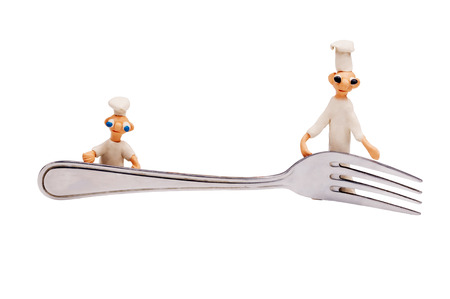 three little cheerful chef made from clay and fork Banco de Imagens