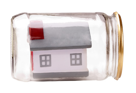 property insurance small toy house model in a closed glass jar metaphor photo