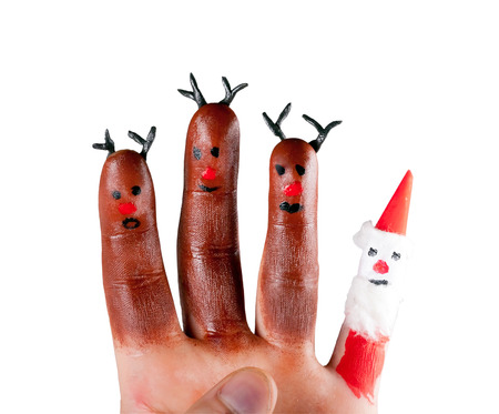 three funny reindeer and Santa  painted on the fingers of a human hand