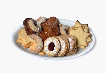 rustical: several kinds of traditional home christmas cookies on a white plate on a white background