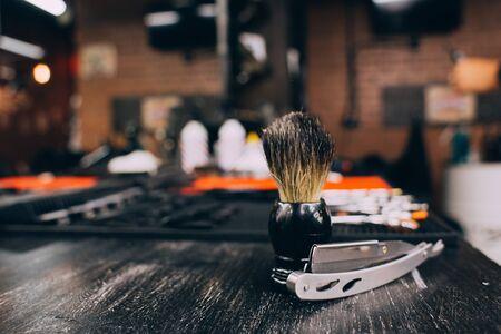 straight razor, brush for shaving beard along with bowl, blurred background of hair salon for men, barber shop.
