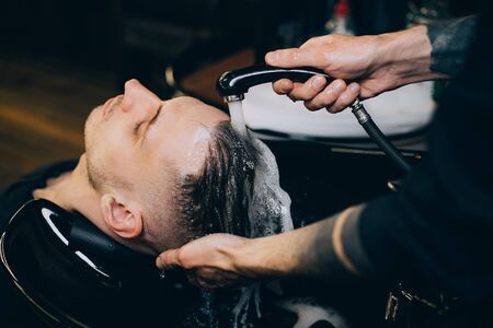 Profile view of bearded man getting his hair washed and his head massaged in hair salon. Cleaning head barber's. Barber men washing client's hair in barbershop or beaty salon. Imagens