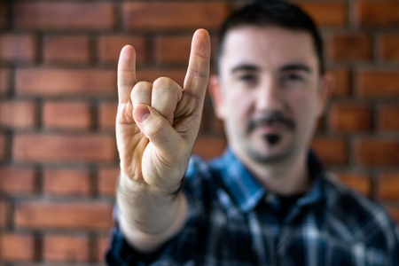 fourties: Young Man in his 30s with trimmed beard showing RNR sign with his hand in front of a red brick wall Stock Photo