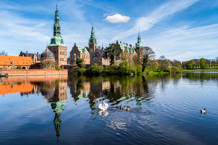 settled: Morning sight of Frederiksborg Castle with the lake reflection, settled in a town Hilerod, north-west of Copenhagen, Denmark. A swan and several ducks swimming in the lake.