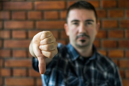 30s: Young man in plaid shirt with trim beard in his 30s showing thumbs down. Selective focus