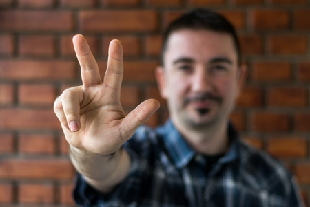 fingers: Young man in his 30s in plaid shirt with trim beard in his 30s showing three fingers. Selective   focus Stock Photo