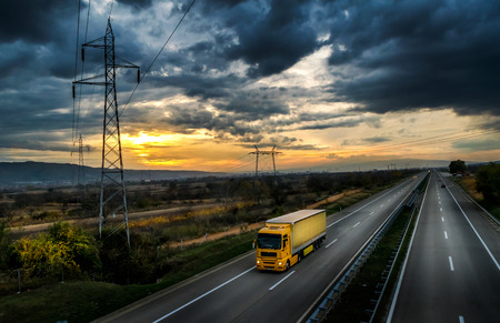 ciężarówka: Autostrada transportu z żółtym samochodem ciężarowym o zachodzie słońca