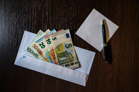 subornation: White envelope with Euro bills over wooden background