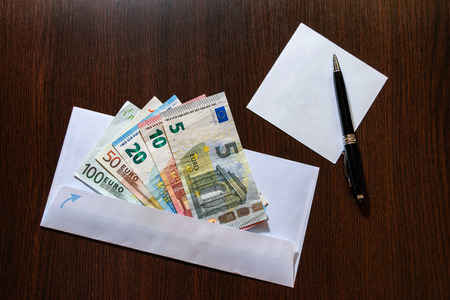 batch of euro: White envelope with Euro bills over wooden background